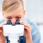 Closeup portrait of young female doctor viewing through microsco